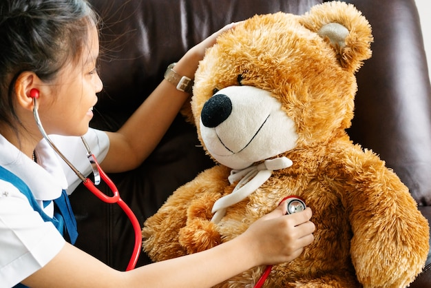 Kleines mädchen, das doktor mit braunem bären und stethoskop lächelt und spielt. kind und gesundheitspflege
