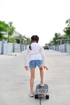 Kleines mädchen, das draußen auf der straße auf skateboard reitet. rückansicht