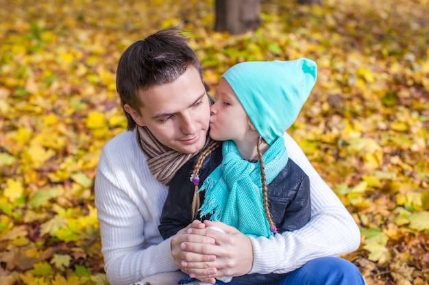 Kleines mädchen, das draußen glücklichen vater im herbstpark küsst