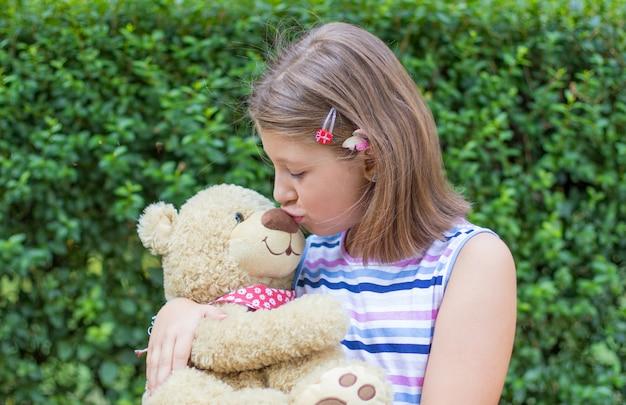 Kleines mädchen, das draußen großen teddybären hält