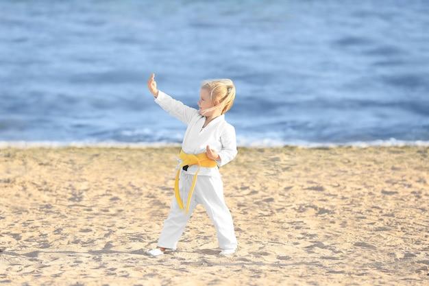Kleines mädchen, das draußen karate übt