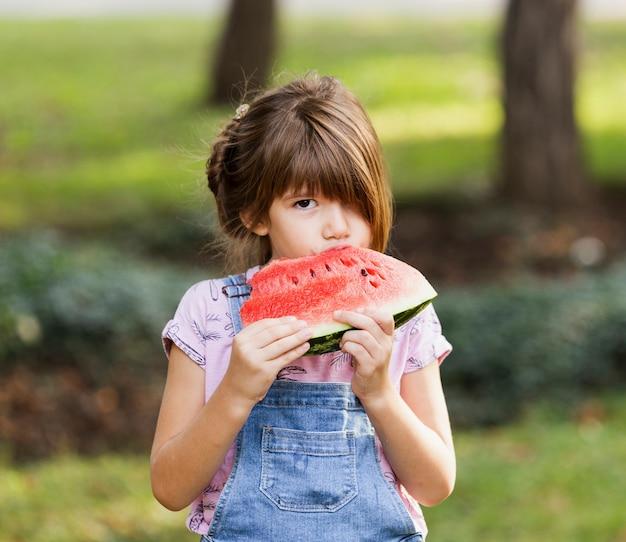 Kleines mädchen, das draußen wassermelonenscheibe genießt