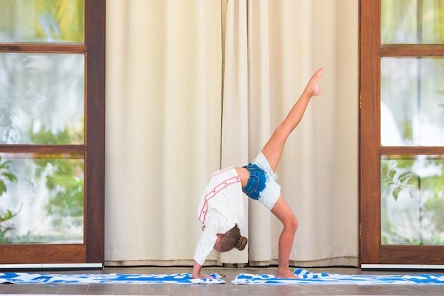 Kleines mädchen, das draußen yogaübung auf terrasse tut