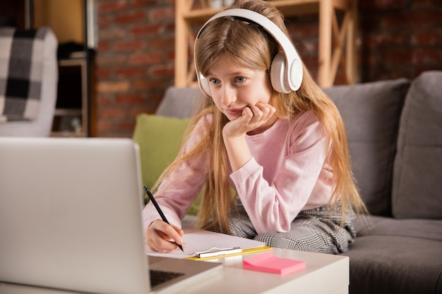 Kleines mädchen, das durch gruppenvideoanruf lernt, videokonferenz mit lehrer benutzt, online-kurs hört.