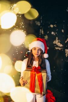 Kleines mädchen, das durch weihnachtsbaum sitzt und geschenke auspackt