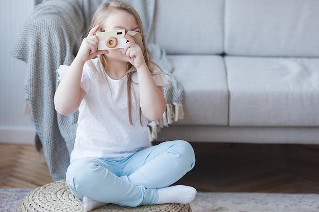 Kleines mädchen, das ein bild macht. nette fotografie innen. entzückendes kind, das mit kamera spielt.