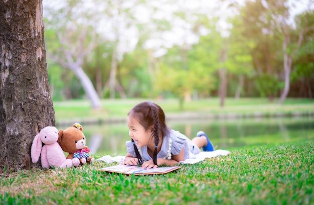 Kleines mädchen, das ein buch beim lügen mit einer puppe liest