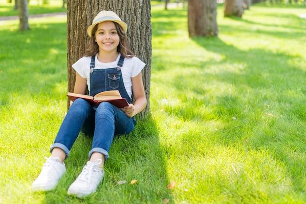 Kleines mädchen, das ein buch beim sitzen auf gras liest