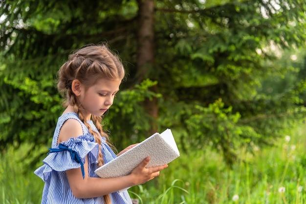 Kleines mädchen, das ein buch im freien liest