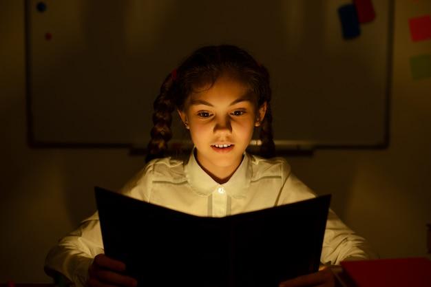 Kleines mädchen, das ein buch im klassenzimmer liest