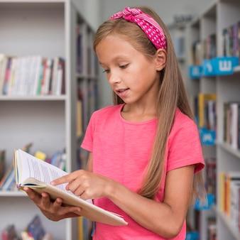 Kleines mädchen, das ein buch in der bibliothek liest