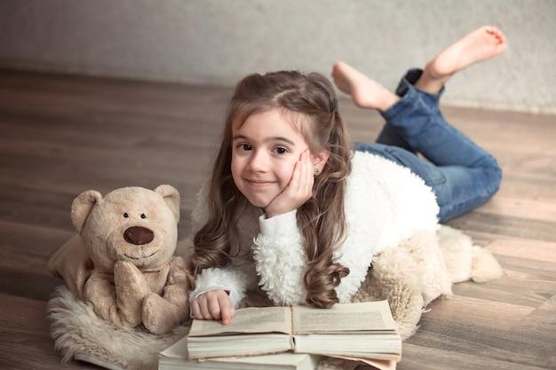 Kleines mädchen, das ein buch mit einem teddybär auf dem boden liest, konzept der entspannung und der freundschaft