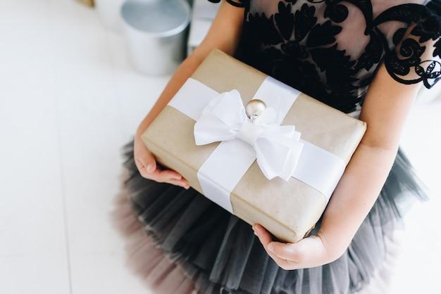 Kleines mädchen, das ein eingewickeltes weihnachtsgeschenk hält