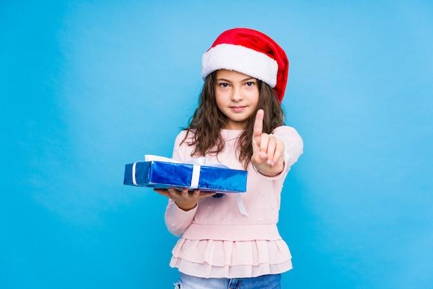 Kleines mädchen, das ein geschenk feiert weihnachtstag hält