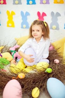 Kleines mädchen, das ein großes ei der ostern-dekoration hält.