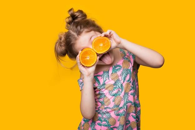 Kleines mädchen, das ein kleid trägt, bedeckt ihre augen mit geschnittenen orangenstücken
