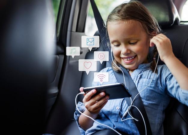 Kleines mädchen, das ein telefon in einem auto benutzt