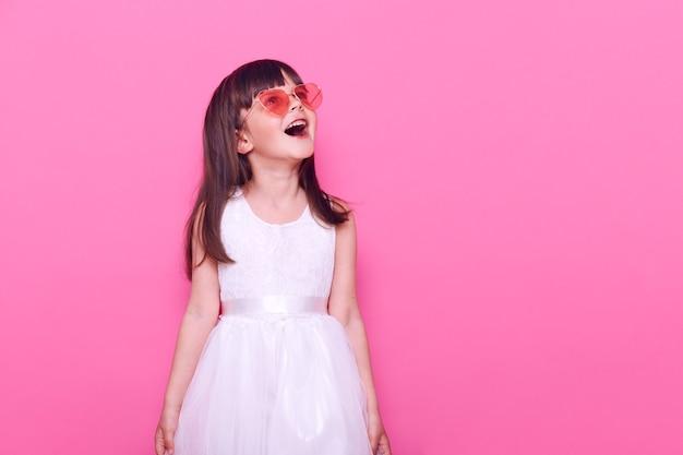 Kleines mädchen, das eine brille in herzform und in einem weißen kleid trägt, aufgeregten gesichtsausdruck hat und mit geöffnetem mund nach oben schaut.