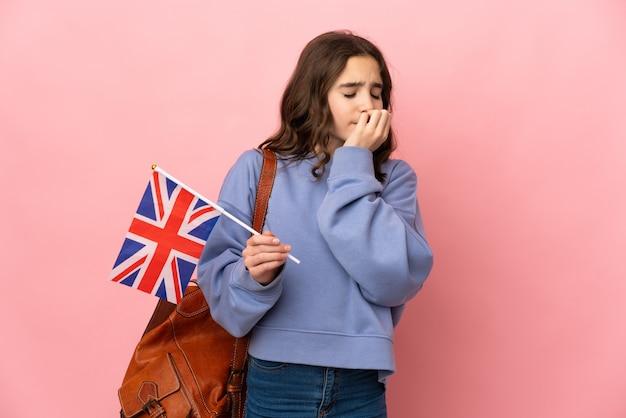 Kleines mädchen, das eine britische flagge hält, die auf rosa wand lokalisiert wird, die zweifel hat