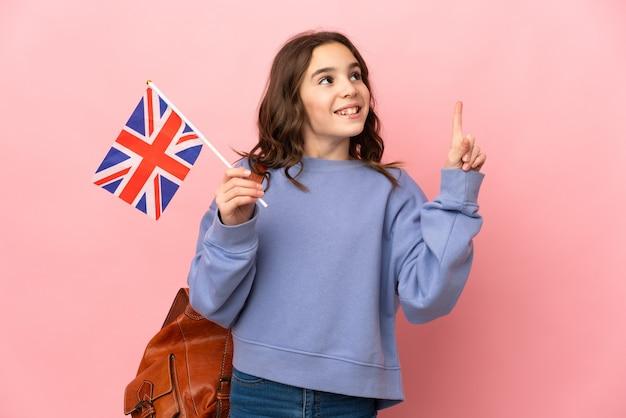 Kleines mädchen, das eine britische flagge lokalisiert auf rosa hintergrund hält, der eine idee denkt, die den finger nach oben zeigt