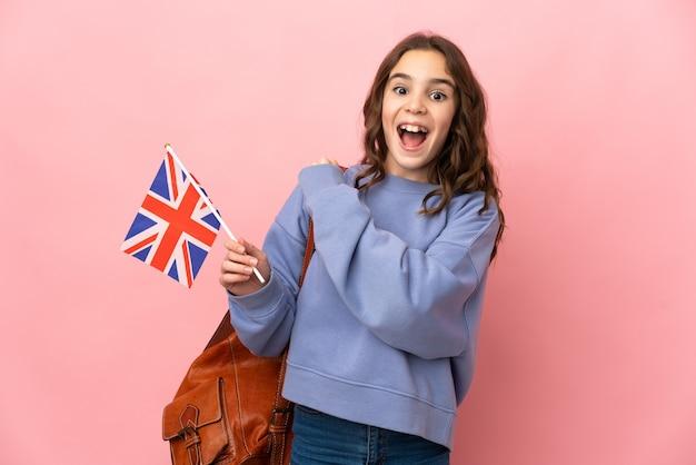 Kleines mädchen, das eine britische flagge lokalisiert auf rosa wand hält, die einen sieg feiert