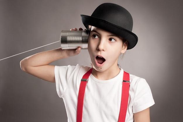 Kleines mädchen, das eine dose als telefon auf grau verwendet