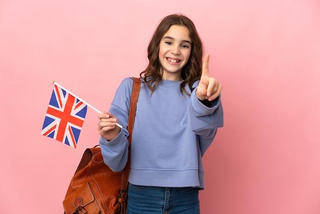 Kleines mädchen, das eine flagge des vereinigten königreichs hält, die auf rosa hintergrund isoliert ist und einen finger zeigt und hebt