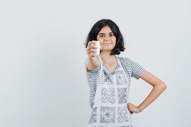 Kleines mädchen, das eine flasche pillen im t-shirt, in der schürze präsentiert und selbstbewusst aussieht.