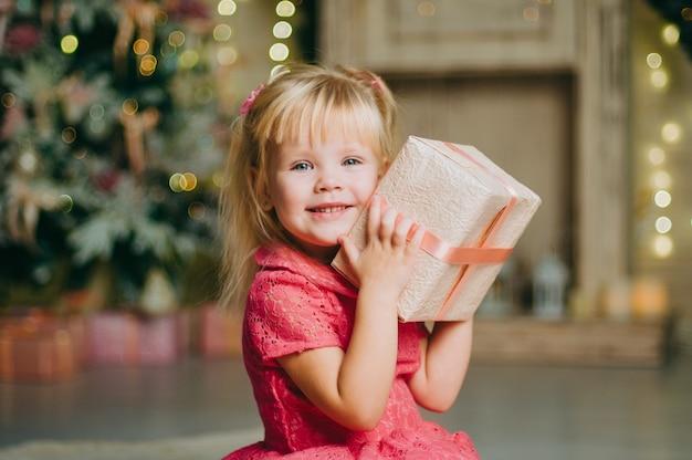 Kleines mädchen, das eine geschenkbox hält