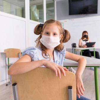Kleines mädchen, das eine gesichtsmaske während der pandemie trägt
