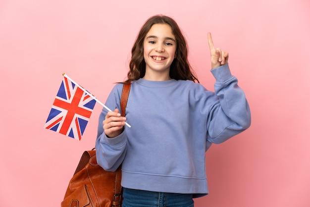 Kleines mädchen, das eine großbritannienflagge lokalisiert auf rosa hintergrund hält, der eine große idee aufzeigt