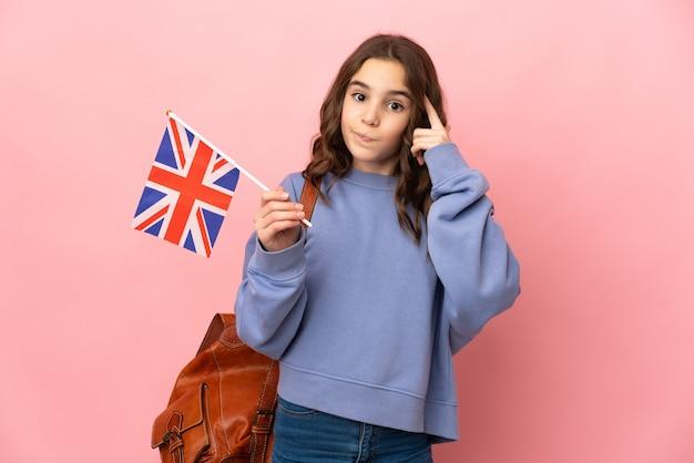 Kleines mädchen, das eine großbritannienflagge lokalisiert auf rosa hintergrund hält, der eine idee denkt