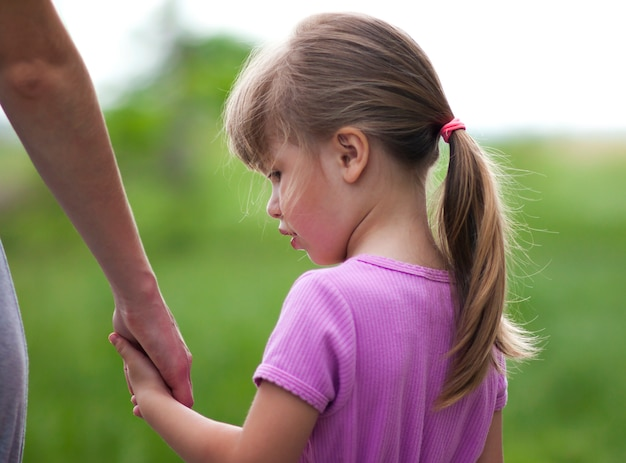 Kleines mädchen, das eine hand ihrer mutter hält. familienbeziehungen konzept.