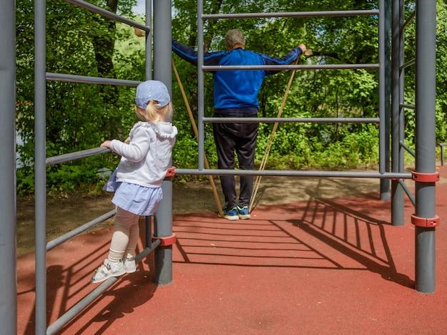 Kleines mädchen, das eine leiter auf einem gesunden lebensstilkonzept des sportplatzes klettert