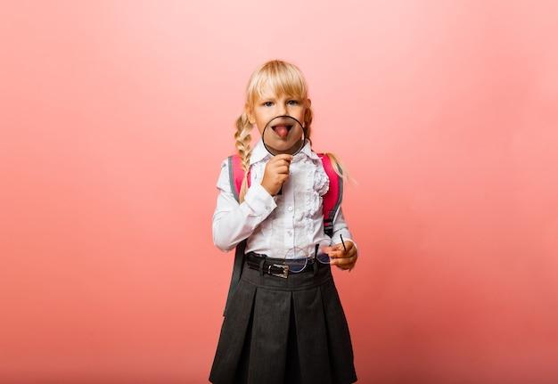 Kleines mädchen, das eine lupe in der nähe ihres mundes hält und ihre zunge auf einem rosa hintergrund zeigt