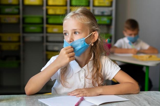 Kleines mädchen, das eine medizinische maske im unterricht trägt