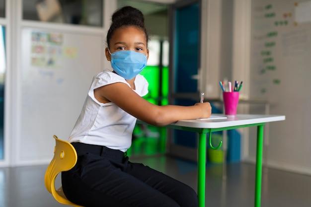 Kleines mädchen, das eine medizinische maske im unterricht verwendet