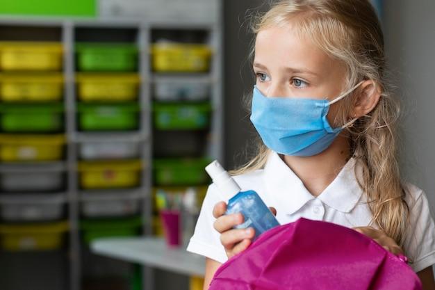 Kleines mädchen, das eine medizinische maske mit kopienraum trägt