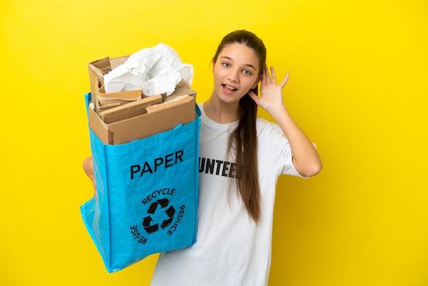Kleines mädchen, das eine recycling-tasche voller papier hält, um über isoliertem gelbem hintergrund zu recyceln und etwas zu hören, indem es die hand auf das ohr legt