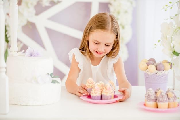 Kleines mädchen, das eine rosa platte mit bonbonkuchen im schokoriegel hält