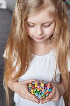 Kleines mädchen, das eine schüssel bunte süße bonbons hält