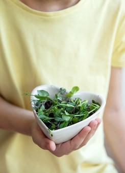 Kleines mädchen, das eine schüssel mit mikrogrün in ihren händen hält. konzept für gesunde ernährung