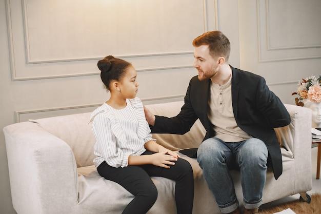 Kleines mädchen, das eine sitzung mit pschoterapist hat. mann, der einen test mit bildern gibt und mit schulmädchen spricht. kindheit.