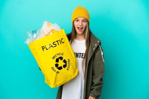 Kleines mädchen, das eine tasche voller plastikflaschen hält, um über isoliertem blauem hintergrund mit überraschendem gesichtsausdruck zu recyceln