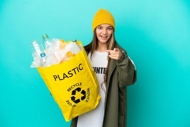 Kleines mädchen, das eine tasche voller plastikflaschen hält, um über isoliertem blauem hintergrund zu recyceln, überrascht und zeigt nach vorne