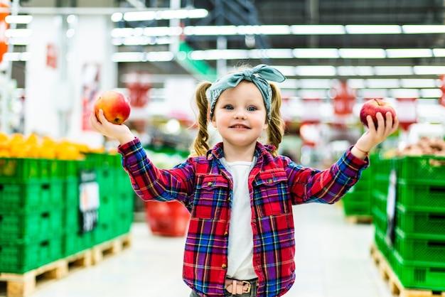 Kleines mädchen, das einen apfel in einem lebensmittelgeschäft oder in einem supermarkt wählt