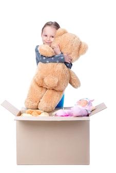 Kleines mädchen, das einen bären in ihren armen und in lächeln hält.