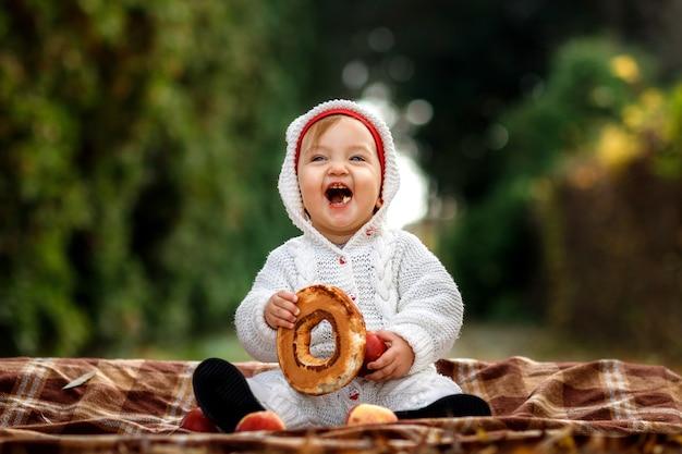 Kleines mädchen, das einen bagel im park isst, der auf einer decke sitzt