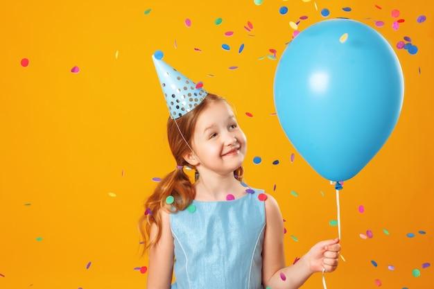 Kleines mädchen, das einen ballon in fallendem konfetti hält.