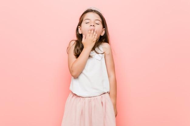Kleines mädchen, das einen gähnenden prinzessinblick trägt, der eine müde geste zeigt, die mund mit hand bedeckt.